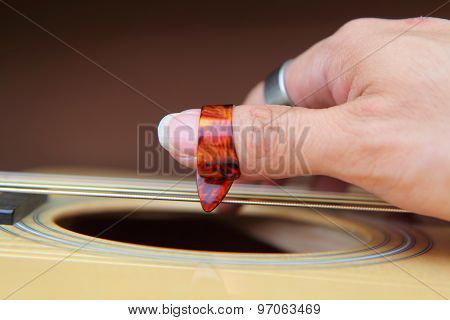 Close up to pick acoustic guitar