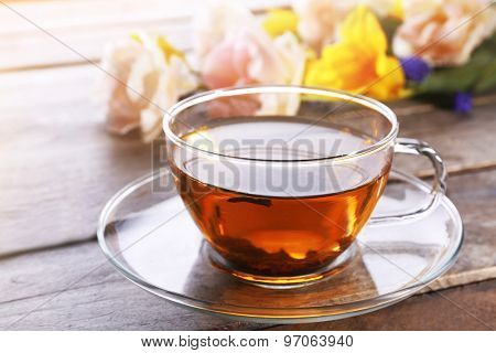 Cup of herbal tea with flowers on wooden table, closeup