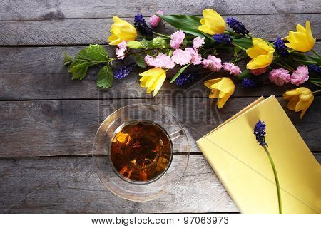 Cup of herbal tea with flowers on wooden table, top view