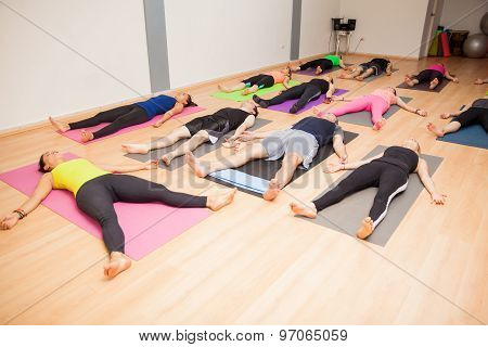 Group Of People Lying Down In Yoga Class