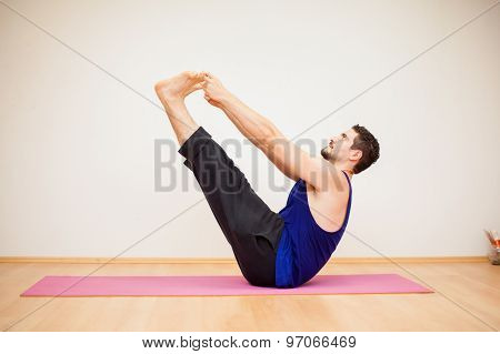 Young Man Doing A Boat Yoga Pose