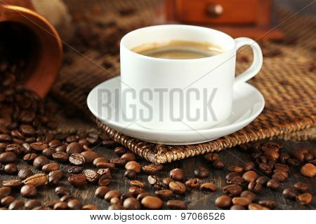 Cup of coffee with beans on table close up