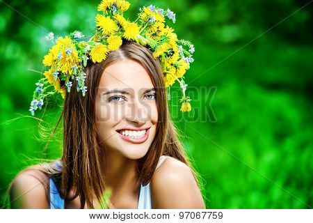 Romantic smiling girl in a wreath of wild flowers sitting on the lawn. Summer life. Beauty.