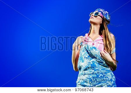 Beautiful fashionable girl wearing jeans clothes posing over blue sky. Summer style. Holidays.