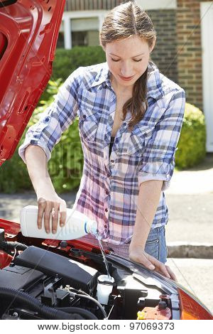 Woman Topping Up Windshield Washer Fluid In Car