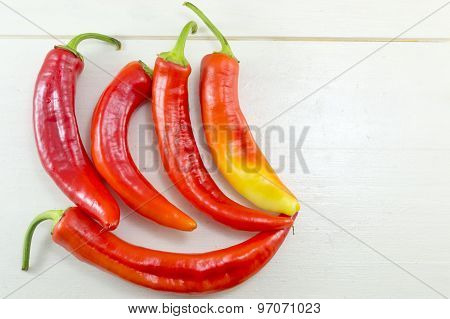 Fresh Crooked Orange And Red Peppers On A White Wooden Table