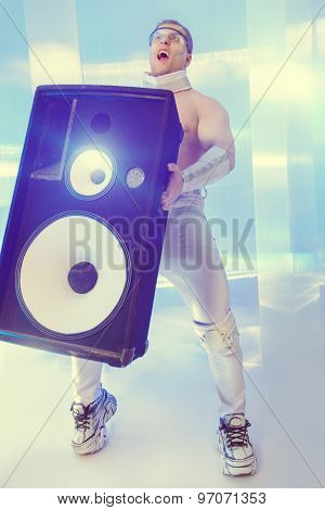 Futuristic muscular man dancing with huge music speakers on a luminous transparent background. Music, technology. Futuristic DJ.