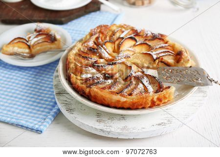 Homemade apple pie on plate, on white wooden table background background