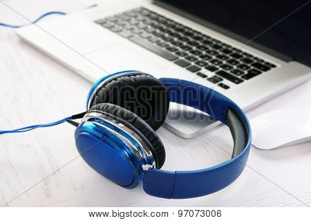 Headphones and other devices on wooden desktop, closeup