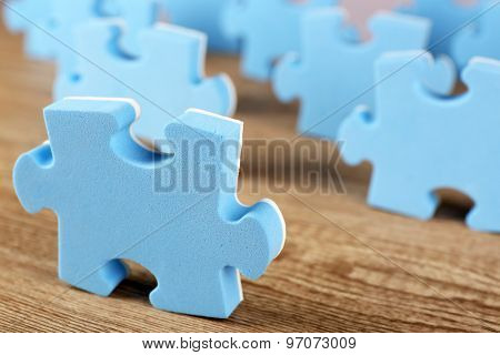Blue puzzle pieces on wooden table, closeup