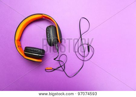 Headphones with clef of cable on purple background