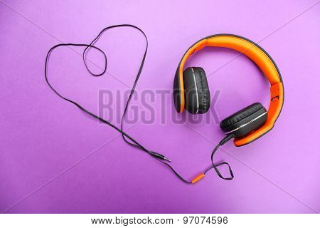 Headphones with heart of cable on purple background