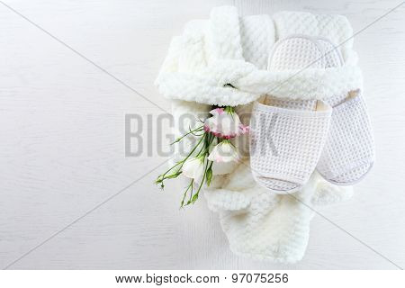 Bath set with white bathrobe and slippers, top view