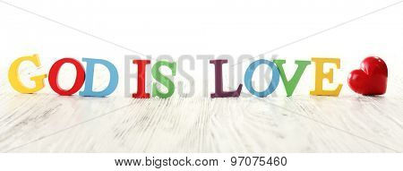 GOD IS LOVE sign illustrated with colorful plastic letters on white wooden background