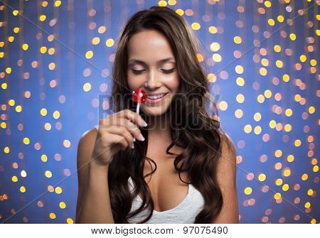 Pretty brunette with lollipop smiling on sparkling background