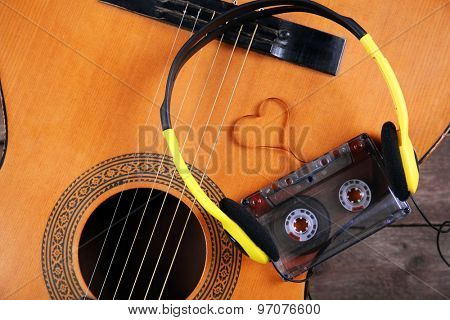 Music recording scene with guitar, cassette and headphones on wooden table, closeup