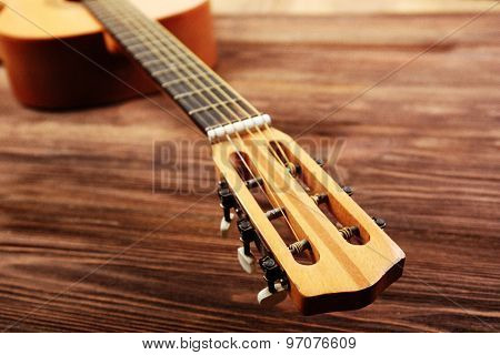 Neck of acoustic guitar on wooden background