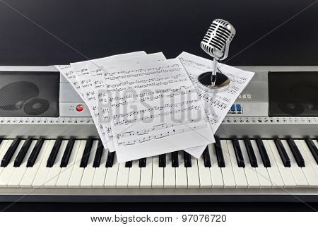 Music notes with microphone on synthesizer on gray background