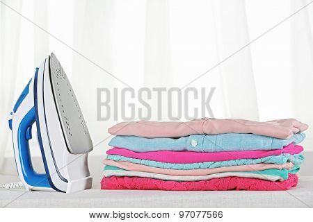 Electronic ironing and pile of clothes on board on curtains background