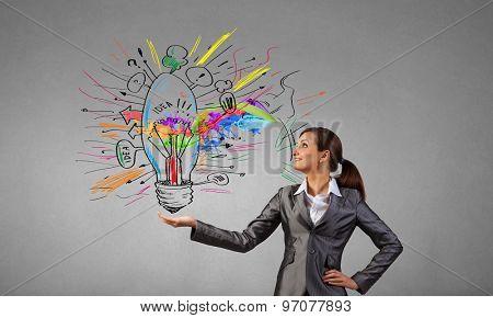 Smiling young businesswoman holding light bulb in palm