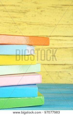 Colorful books on yellow wooden background