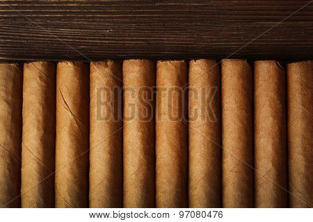 Cigars on wooden table, top view