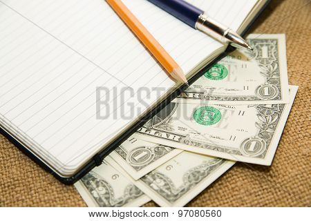 Opened Notebook, Pencil, Pen And Money On The Old Tissue