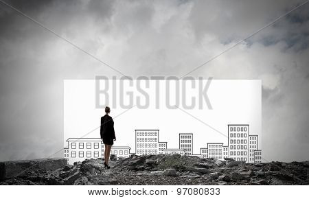 Rear view of businesswoman looking at banner with construction sketches