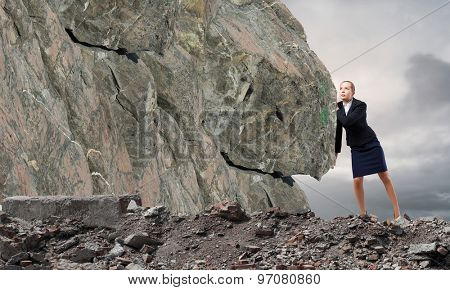 Young businesswoman making effort to move huge stone