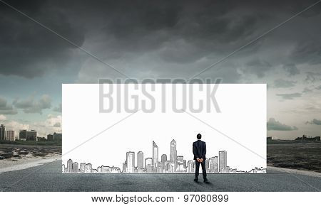 Rear view of businessman looking at banner with construction sketches