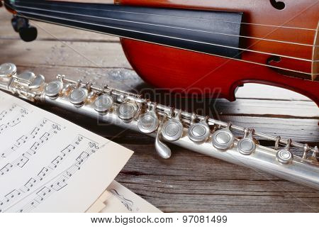 Flute and violin with music notes on wooden table close up