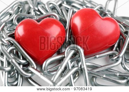 Two red hearts with metal chain, closeup