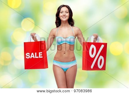 people, fashion, swimwear, summer sale and beach concept - happy young woman in bikini swimsuit with red shopping bags over green holidays lights background