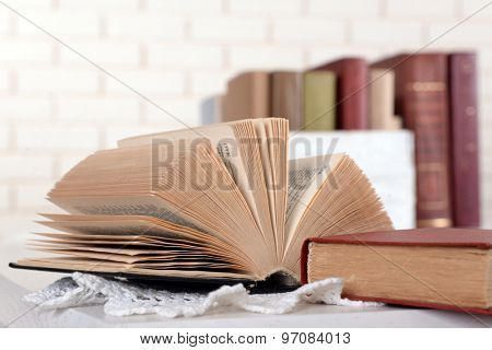 Heap of old books on brick wall background