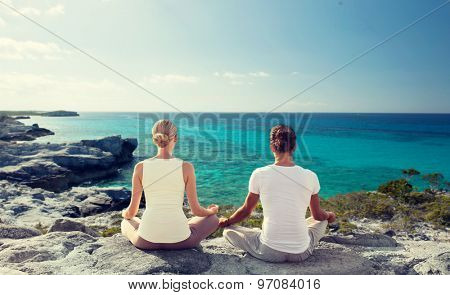 fitness, yoga, people and lifestyle concept - couple meditating on beach from back