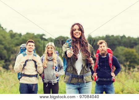 travel, tourism, hike, gesture and people concept - group of smiling friends with backpacks standing and showing thumbs up outdoors