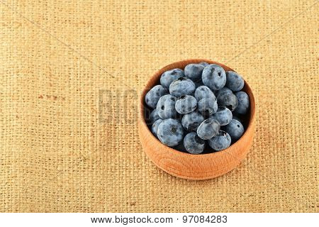 Handful Of Blueberries In Wooden Bowl On Canvas