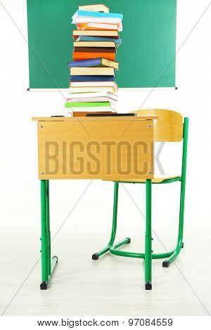 Wooden desk with books and chair in class on blackboard background