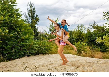Best Friends Have Fun At The Beach. Piggyback