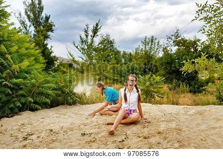 Best Friends Sitting On Sand At Beach.