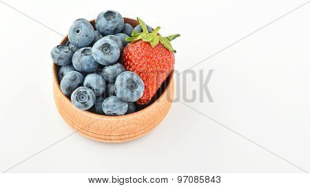 Blueberries And One Strawberry In Wooden Bowl Isolated On White
