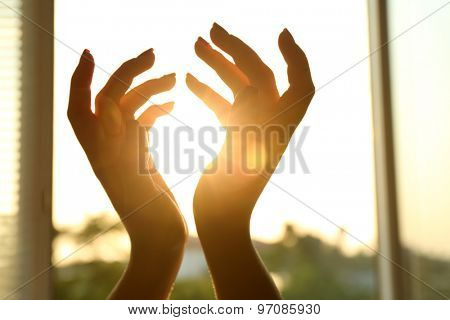 Female hands over sunset sky background