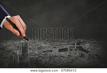 Close up of hand drawing urban buildings with marker