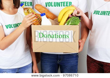 Volunteer holding donation box with food, closeup