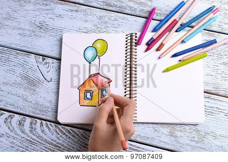Female hand drawing colorful house in notebook on wooden table background