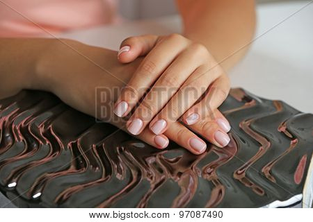 Woman hands with french manicure on shiny surface close-up