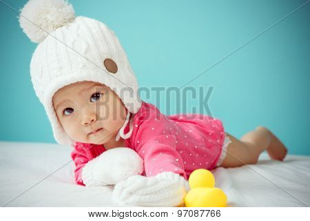 Baby Wearing White Knitted Beanie In Front Of Blue Background
