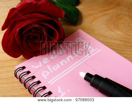 Pink notepad with wedding planning and rose.