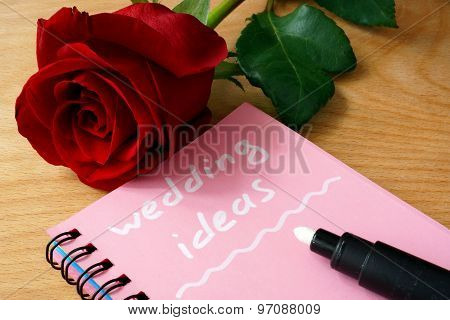 Pink notepad with wedding ideas and rose.