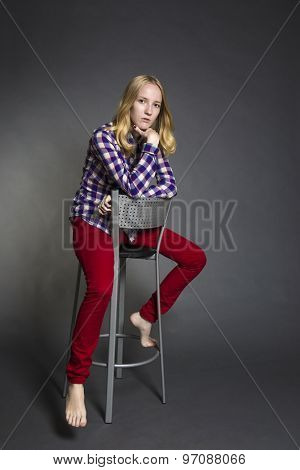 Studio portrait of a teenage girl sitting on a chair